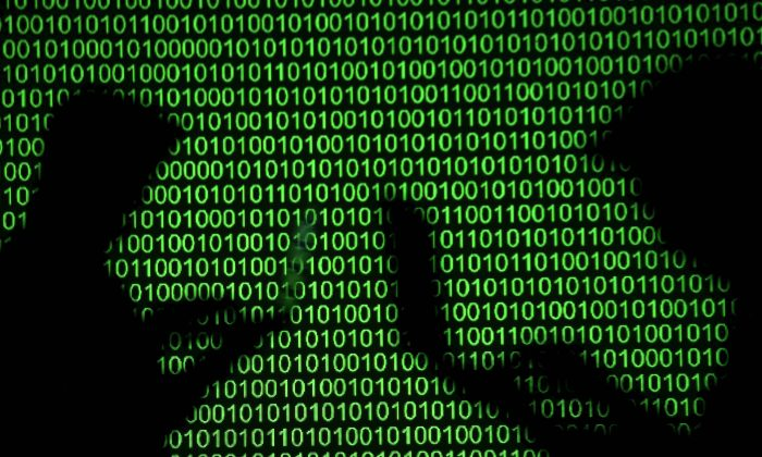 Silhouettes of laptop users next to a screen projection of binary code in this picture illustration taken on March 28, 2018. (Reuters/Dado Ruvic/Illustration/File Photo/File Photo)
