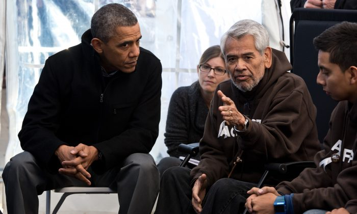 Former President Barack Obama (L) listens to Eliseo Medina and other people taking part in the Fast for Families on the National Mall in Washington on Nov. 29, 2013. Obama offered support for those fasting for immigration reform. (NICHOLAS KAMM/AFP/Getty Images)