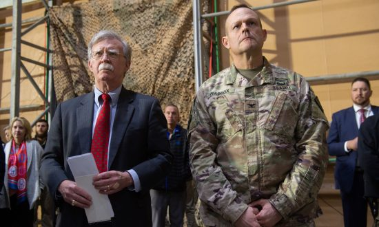 US National Security Adviser John Bolton (L) listens as US President Donald Trump speaks to members of the US military  during an unannounced trip to Al Asad Air Base in Iraq on Dec. 26, 2018. (Saul Loeb/AFP/Getty Images)