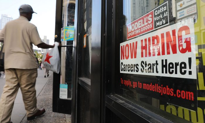 A now hiring sign is displayed in the window of a Brooklyn business in New York on Oct. 5, 2018. (Spencer Platt/Getty Images)