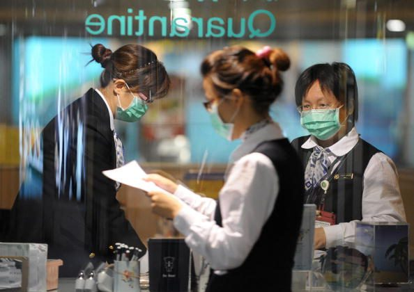 Masked Taiwan government quarantine staffs stand by a check point at the Taoyuan International Airport on April 28, 2009. (Sam Yeh/AFP/Getty Images)