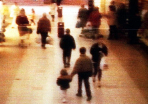 A surveillance camera shows the abduction of 2-year-old James Bulger from the Bootle Strand shopping mall, on Feb. 12, 1993, at 3:42 p.m. near Liverpool, England. Bulger holds the hand of Jon Venables, one of two 10-year-old boys later convicted of his torture and murder. (BWP Media via Getty Images)
