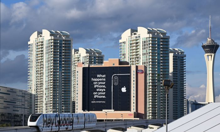 "A monorail train plastered with a Google advertisement passes a giant sign from Apple on a building as preparations are underway for the CES 2019 show, Jan. 6, 2019, in Las Vegas, Nevada.  Apple is taking a shot at rivals such as Google on the data privacy front with the message reading ""What happens on your iPhone stays on your iPhone.""  (ROBYN BECK/AFP/Getty Images)"