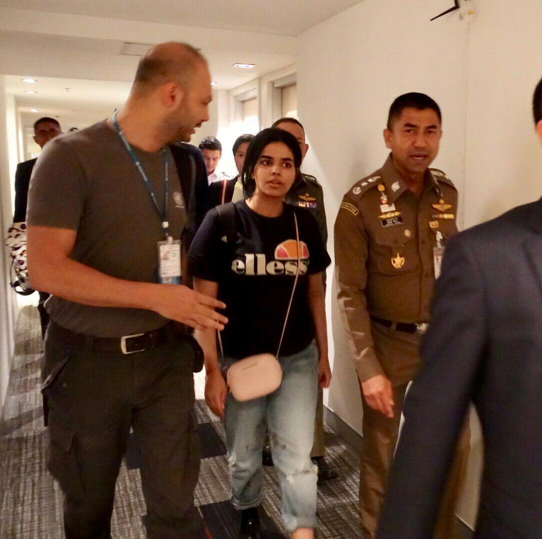 Saudi teen Rahaf Mohammed al-Qunun walks with Thai immigration authorities at a hotel inside Suvarnabhumi Airport in Bangkok