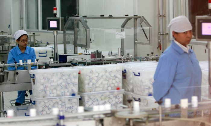 Chinese workers watch the production line of pill capsules at a factory in Beijing on Aug. 3 2007.  The United States will help China improve the safety of its food and drug exports, the U.S. health chief said in a statement released on Aug. 3 after a string of health scandals surrounding Chinese-made goods. (Teh Eng Koon/AFP/Getty Images)