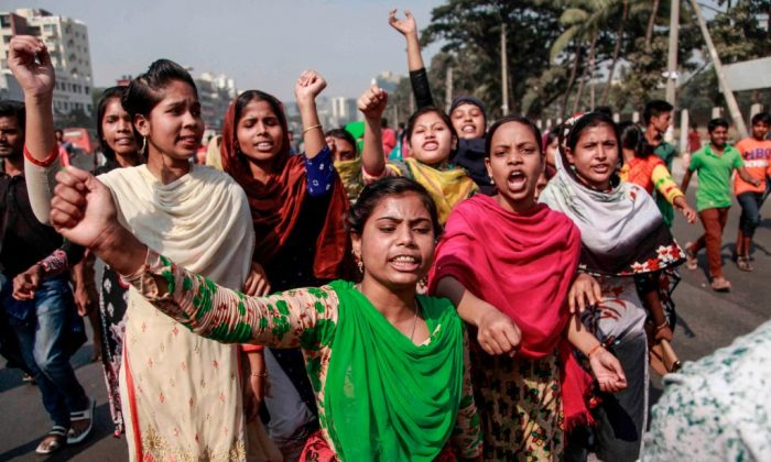 Bangladeshi striking garments workers march in the streets of Dhaka on Jan. 8, 2019 during a third day of demonstration to demand wage hikes. - Bangladesh's 4,500 textile and clothing factories exported more than $30 billion worth of apparel last year, making clothing for retailers such as H&M, Walmart, Tesco, Carrefour and Aldi. (Abdullah Apu/AFP/Getty Images)