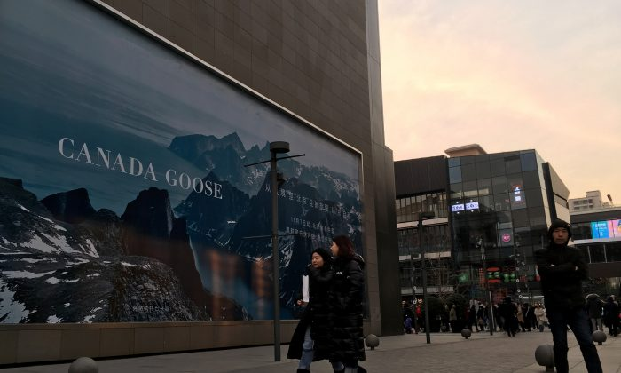 People walk past an advertisement near the newly opened flagship store of Canadian luxury parka maker Canada Goose, in the Sanlitun area of Beijing on December 31, 2018. (REUTERS/Martin Pollard)