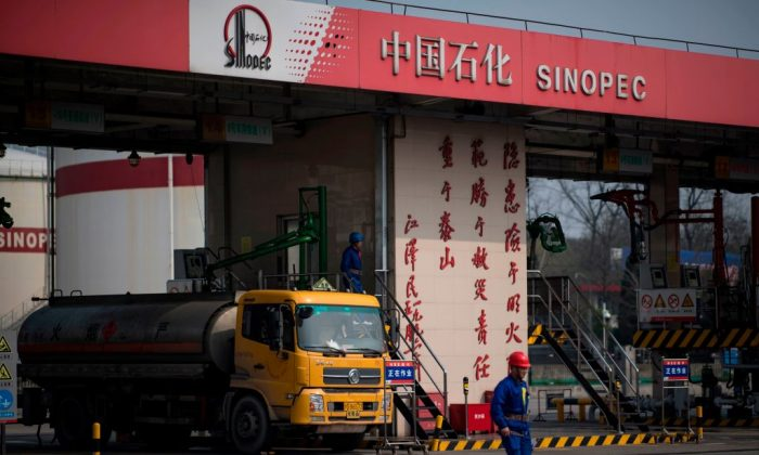 A man works at a gas station of Sinopec in Shanghai on March 22, 2018. (Johannes Eisele/AFP/Getty Images)