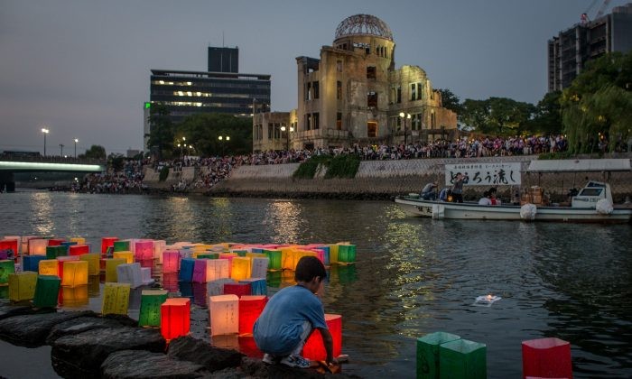 A boy floats a candle lit paper lantern on the river in front of the Atomic Bomb Dome during 70th anniversary activities, commemorating the atomic bombing of Hiroshima, Japan, at the Hiroshima Peace Memorial Park on Aug. 6, 2015. (Chris McGrath/Getty Images)