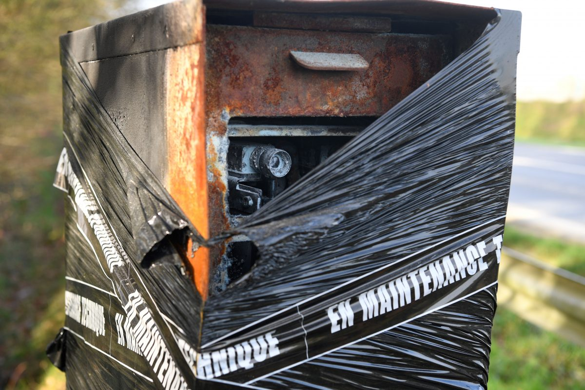 """A burnt speed camera covered with plastic and tape reading """"under technical maintenance"""""""