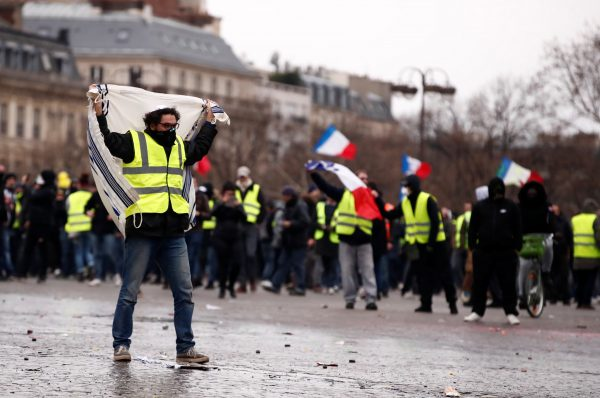"""Protesters wearing yellow vests take part in a demonstration by the """"yellow vests"""" movement near the Arc de Triomphe in Paris"""