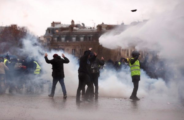 """Protesters walk through tear gas during a demonstration of the """"yellow vests"""" movement near the Arc de Triomphe in Paris"""