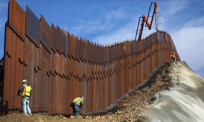 A construction crew works as new sections of the U.S.-Mexico border barrier are installed replacing smaller fences, as seen from Tijuana, Mexico,on Jan. 11, 2019. (Mario Tama/Getty Images)
