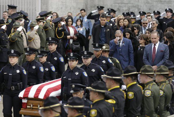 Family members follow the flag draped coffin of Davis Police Officer Natalie Corona