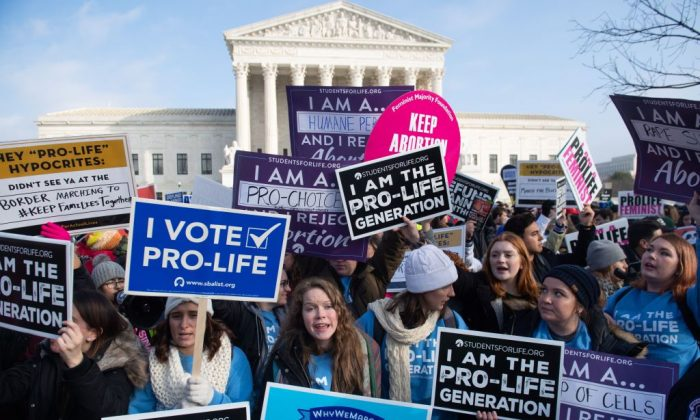 "Pro-choice activists hold signs in response to anti-abortion activists participating in the ""March for Life,"" an annual event to mark the anniversary of the 1973 Supreme Court case Roe v. Wade, which legalized abortion in the US, outside the US Supreme Court in Washington on Jan. 18, 2019. (SAUL LOEB/AFP/Getty Images)"