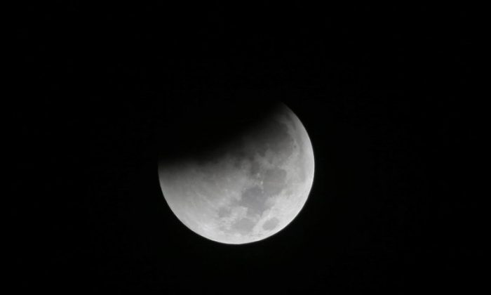 In this Saturday Aug. 28, 2018 file photo, Earth starts to cast its shadow on the moon during a complete lunar eclipse seen from Jakarta, Indonesia. (AP Photo/Tatan Syuflana)