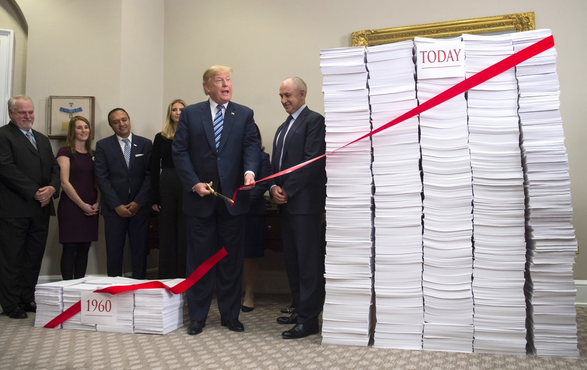 140d693cd29 President Donald Trump uses gold scissors to cut a red tape tied between  two stacks of papers representing the government regulations of the 1960s  (L) and ...