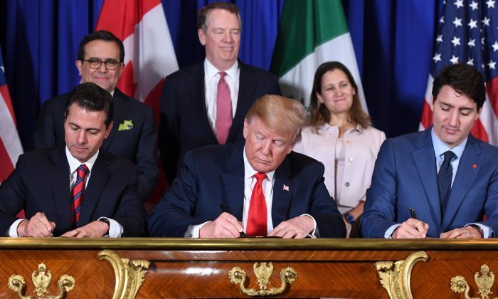 Mexico's President Enrique Peña Nieto (L), President Donald Trump (C), and Canadian Prime Minister Justin Trudeau sign the USMCA agreement in Buenos Aires on Nov. 30, 2018. (Saul Loeb/AFP/Getty Images)