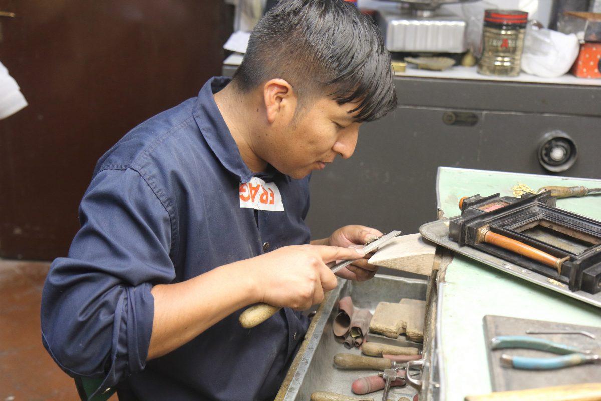 Man files metal in workshop