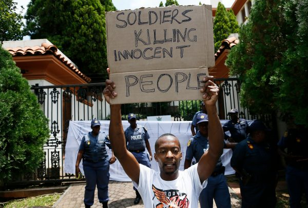 A protester holds a placard during a demonstration of Zimbabwean citizens outside the Zimbabwean Embassy in Pretoria, South Africa, on Jan. 16, 2019. (Phill Magakoe/AFP/Getty Images)