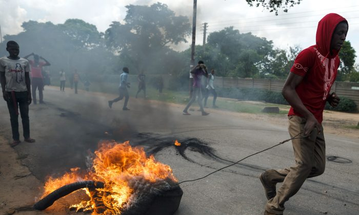 A man drags a burning tire as angry protesters barricade the main route to Zimbabwe's capital Harare from Epworth township on Jan. 14, 2019. (Jekesai Njikizana/AFP/Getty Images)