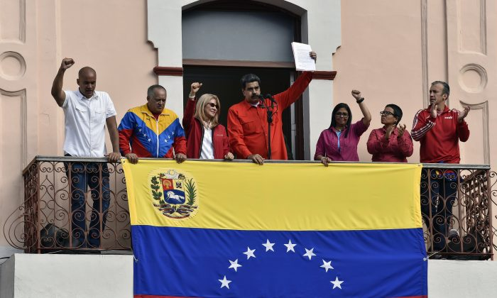 Venezuela's President Nicolas Maduro (C), speaks to a crowd of supporters flanked by his wife Cilia Flores (2-L), Venezuelan Vice-president Delcy Rodriguez (R) the head of Venezuela's Constituent Assembly Diosdado Cabello, along with other members of the government, to announce his is breaking off diplomatic ties with the United States, during a gathering in Caracas on Jan. 23, 2019. (Luis Robayo/AFP/Getty Images)