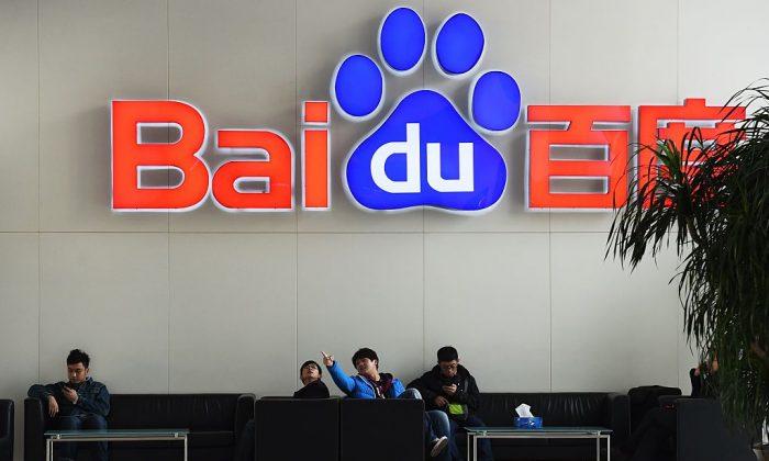 People sit below a Baidu logo at the Baidu headquarters in Beijing on Dec. 17, 2014. (Greg Baker/AFP/Getty Images)