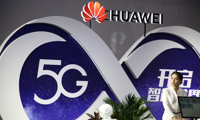 A woman stands at the booth of Huawei featuring 5G technology at the PT Expo in Beijing, China on Sept. 28, 2018. (Reuters)
