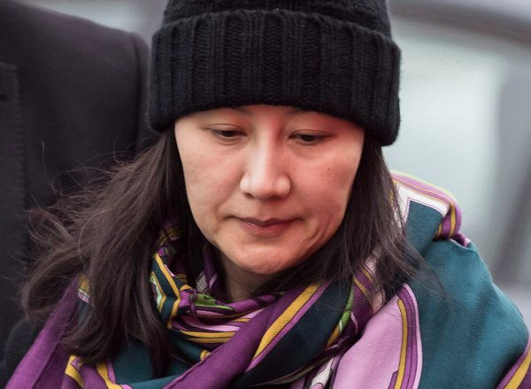 Huawei chief financial officer Meng Wanzhou is escorted by her private security detail while arriving at a parole office, in Vancouver, on Dec. 12, 2018. (The Canadian Press/Darryl Dyck)
