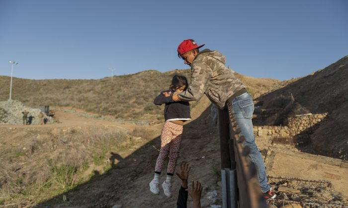 A migrant from Honduras passes a child to her father after jumping the border fence to reach the US side in San Diego, Calif., on Jan. 3, 2019. (Daniel Ochoa de Olza/AP Photo)