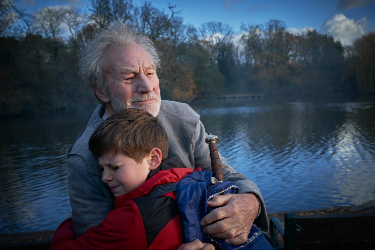 Old man in boy and a lake