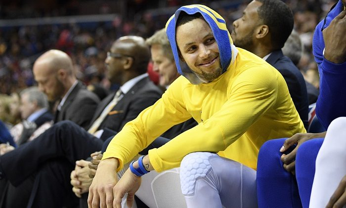 Golden State Warriors guard Stephen Curry smiles on the bench during the first half of the team's NBA basketball game against the Washington Wizards,in Washington, on Jan. 24, 2019. (Nick Wass/AP Photo)