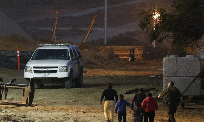 Illegal aliens are escorted by a U.S. Border Patrol agent as they are detained after climbing over the border wall from Playas de Tijuana, Mexico, to San Ysidro, Calif., on Dec. 3, 2018. (Rebecca Blackwell/AP Photo)