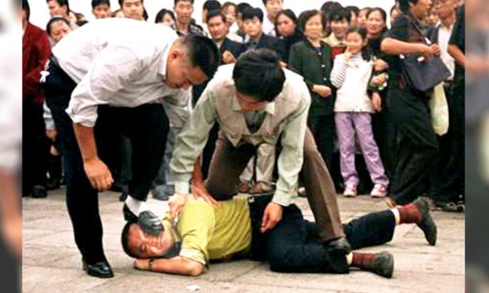 File photo shows plain-clothes policemen from the Chinese Communist regime violently pin down an innocent Falun Gong practitioner in Tiananmen Square. (Courtesy of Minghui)