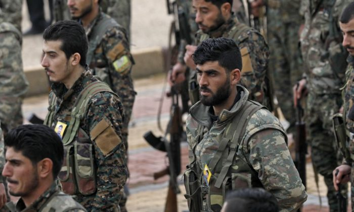 Fighters from the Syrian Democratic Forces (SDF) attend the funeral of a fellow fighter, who was killed while fighting against ISIS in northeastern Syrian Kurdish-majority city of Qamishli, on Jan. 18, 2019. (Delil Souleiman/AFP/Getty Images)