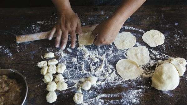 Hands roll out homemade dumpling dough on floured surface