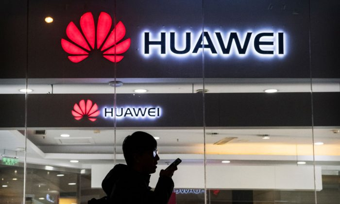 A pedestrian talks on the phone while walking past a Huawei store in Beijing on Jan. 29, 2019. (Kevin Frayer/Getty Images)