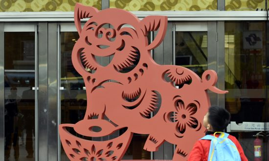 A boy looks at a pig-shaped decoration in front of a local department store to mark the coming Lunar New Year in Taipei, Taiwan on Jan. 23 2019. The Lunar New Year will begin on Feb. 5 and will mark the start of the Year of the Pig. (Sam Yeh/AFP/Getty Images)