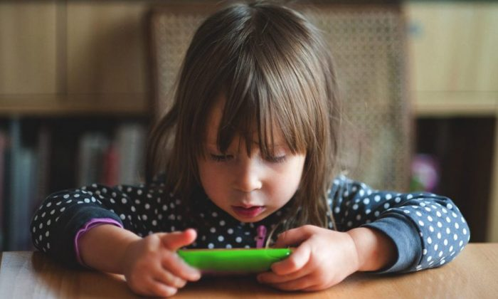 Hours can slip by as children quietly play games on phones and tablets. (Getty Images)