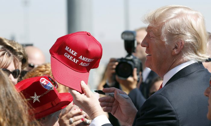 """In this Aug. 23, 2017 file photo, President Donald Trump hands a signed """"Make America Great Again,"""" hat back to a supporter in Reno, Nev. An award-winning cookbook author and California restaurant owner says anyone wearing a red """"Make America Great Again"""" baseball cap will be refused service at his restaurant. J. Kenji Lopez-Alt is a chef-partner of the Wursthall restaurant in San Mateo and says in a tweet Sunday, Jan. 27, 2019, that he views the hats as symbols of intolerance and hate. (AP Photo/Alex Brandon, File)"""