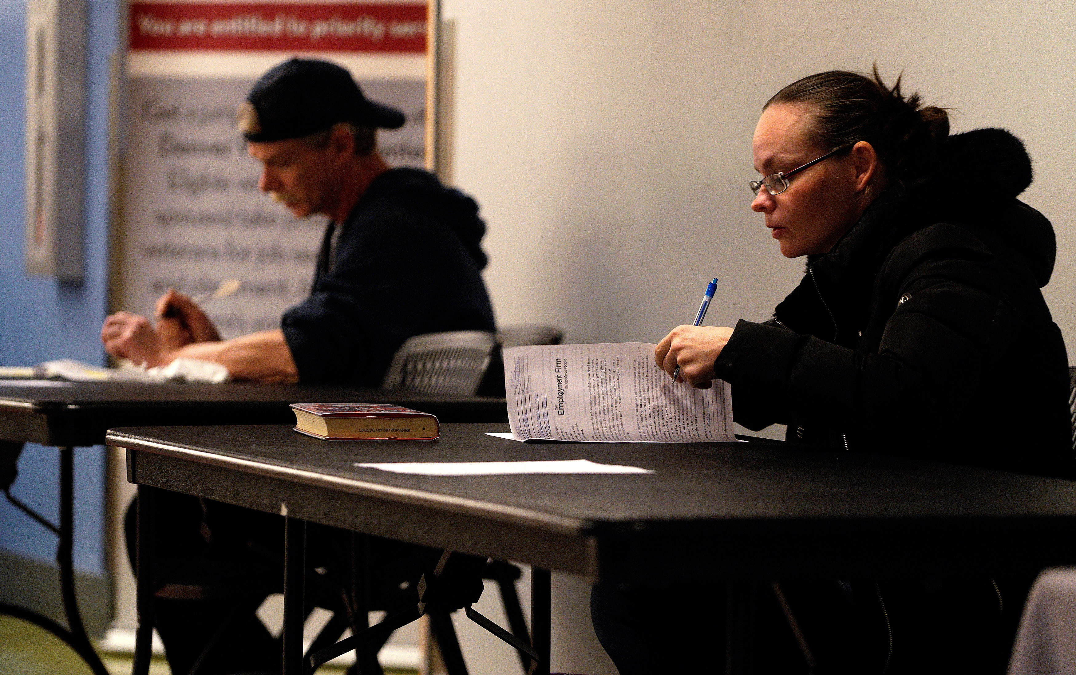 Job seekers fill out applications at a job fair at the Denver Workforce Center in Denver