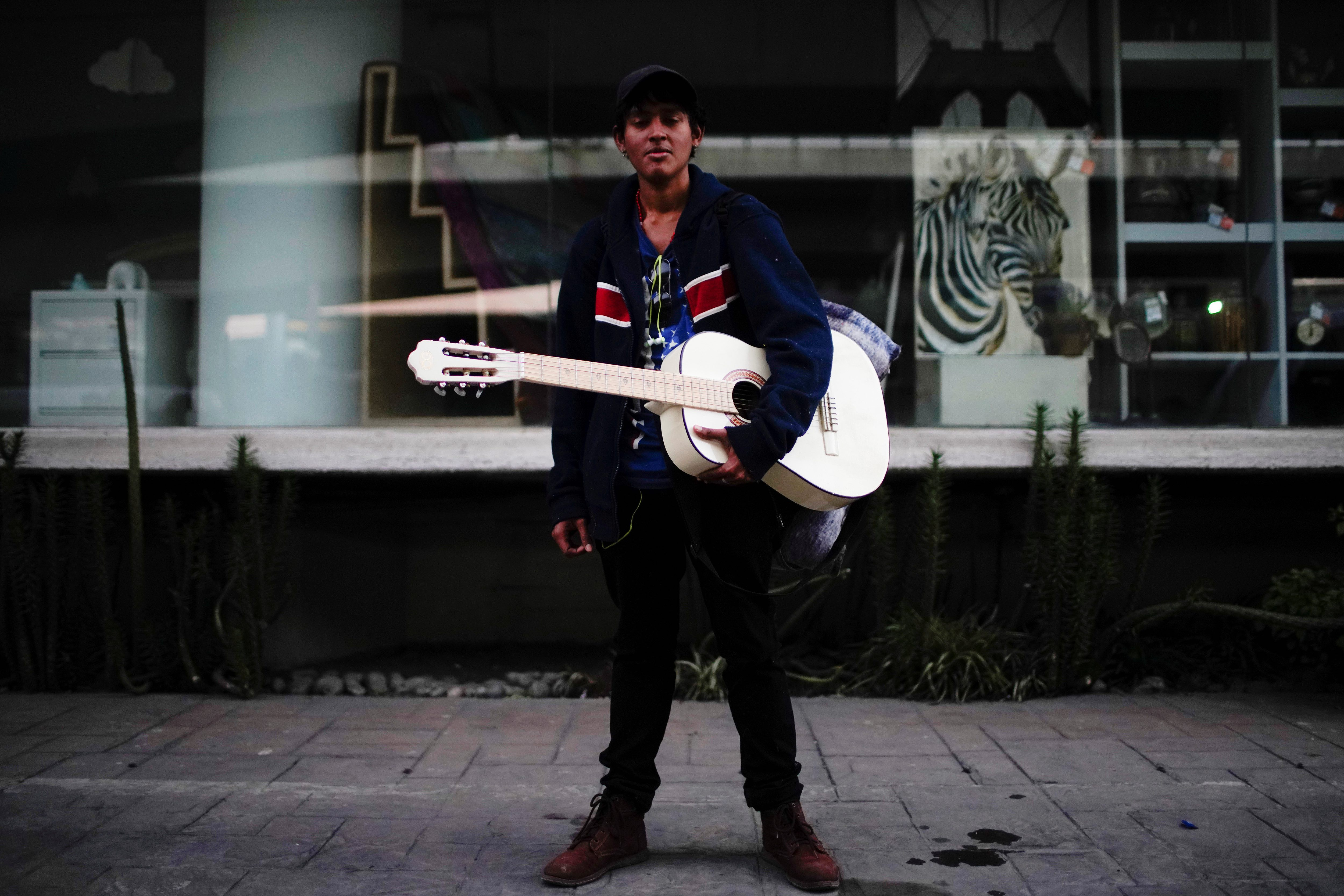 Migrant musician Cristian Martinez from El Salvador, poses for a photo during his journey towards the United States, in Mexico City