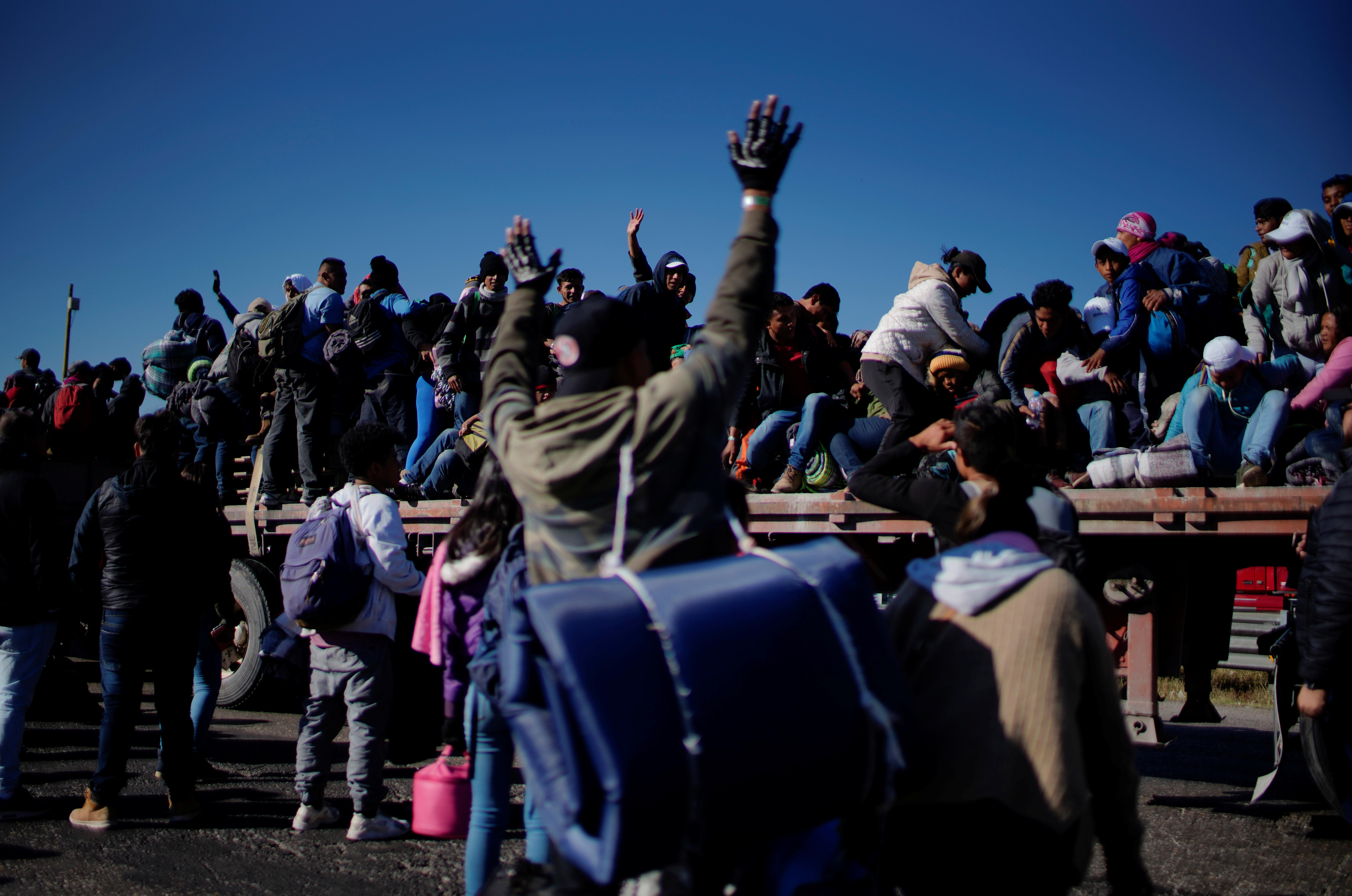 Migrants react as they pass by in the back of a truck during their journey towards the United States, in Mexico City