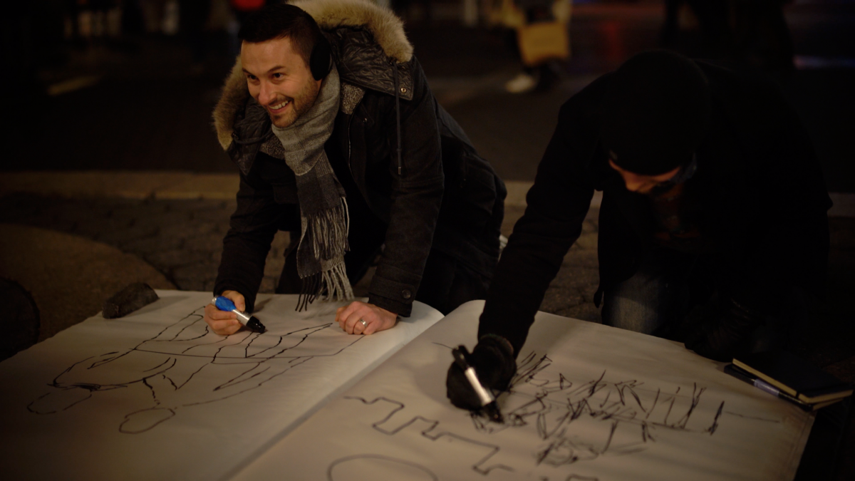 """One of the artists in the """"Sketchbook Vol. 1"""" exhibition, Nicholas Sanchez participates in the giant sketchbook drawing competition in Union Square, New York on January 18. (Paul-Emile Cendron/Sugarlift)."""