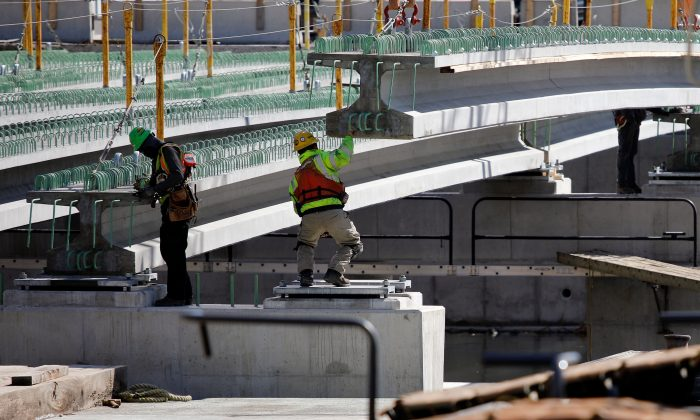 Construction workers guide a piece of a bridge in to place in Baltimore, Md., on March 26, 2018. (David Gannon/AFP/Getty Images)