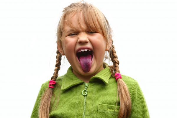 Girl showing her tongue after eating bilberries