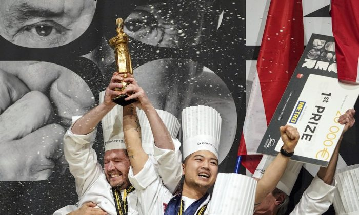 "Kenneth Toft-Hansen of Denmark (L), celebrates on the podium with his commis Christian Wellendorf (C), and their teammates, after winning the final of the ""Bocuse d'Or"" (Golden Bocuse) trophy, in Lyon, central France, on Jan. 30, 2019. (AP Photo/Laurent Cipriani)"