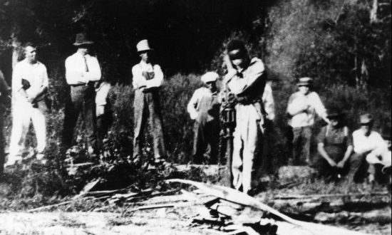 3rd October 1925: A gang of white men gather around J D Ivy, a black man they have blindfolded and tied to a stake in a forest in Georgia, USA. Hulton Archive/Getty Images