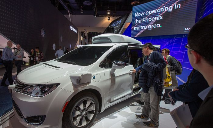 People look at a Waymo self-driving car during CES 2019 in Las Vegas on Jan. 9, 2019.