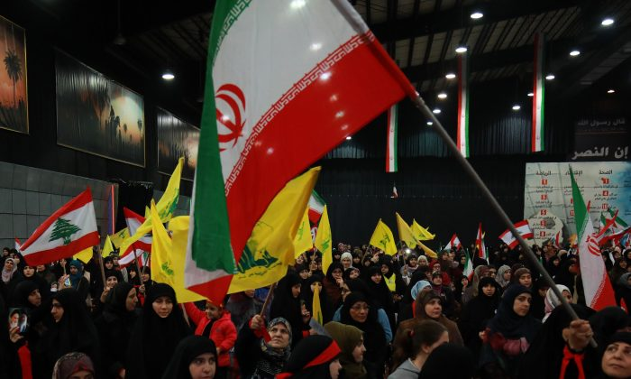 Supporters of Lebanon's Shiite movement Hezbollah wave national, Iranian as well as the movement's yellow flag during celebrations marking the 40th anniversary of the Iranian revolution in the capital Beirut's southern suburbs on February 6, 2019. ANWAR AMRO/AFP/Getty Images